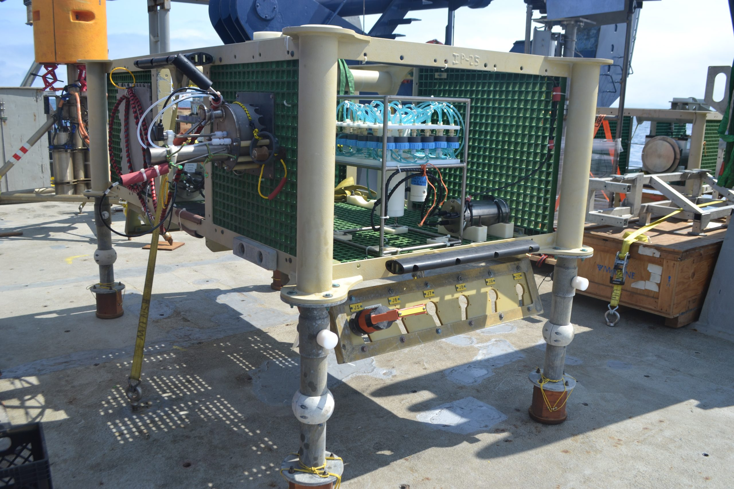 Pre-deployment deck photo of fluid- and microbial-DNA samplers RASFLA/PPSDNA, inside a seafloor-frame, before deployment in the International District Hydrothermal Field, on dive J2-1190 during VISIONS'19. The fluid sampler is attached to a saddle on the left side of the frame. Photo Credit: M. Elend; University of Washington; V19