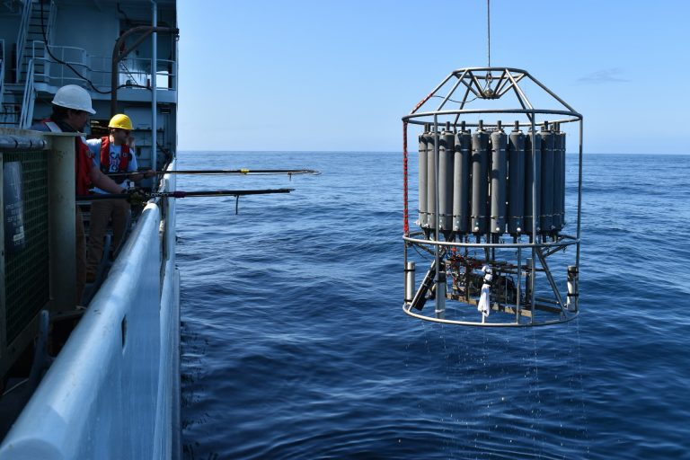 Under beautiful skies, a CTD cast is conducted for follow-on calibration of instruments on the Shallow Profiler Moorings and some seafloor instruments. Water is also collected for turning of HPIES instruments. Credit: M. Elend, University of Washington. V20