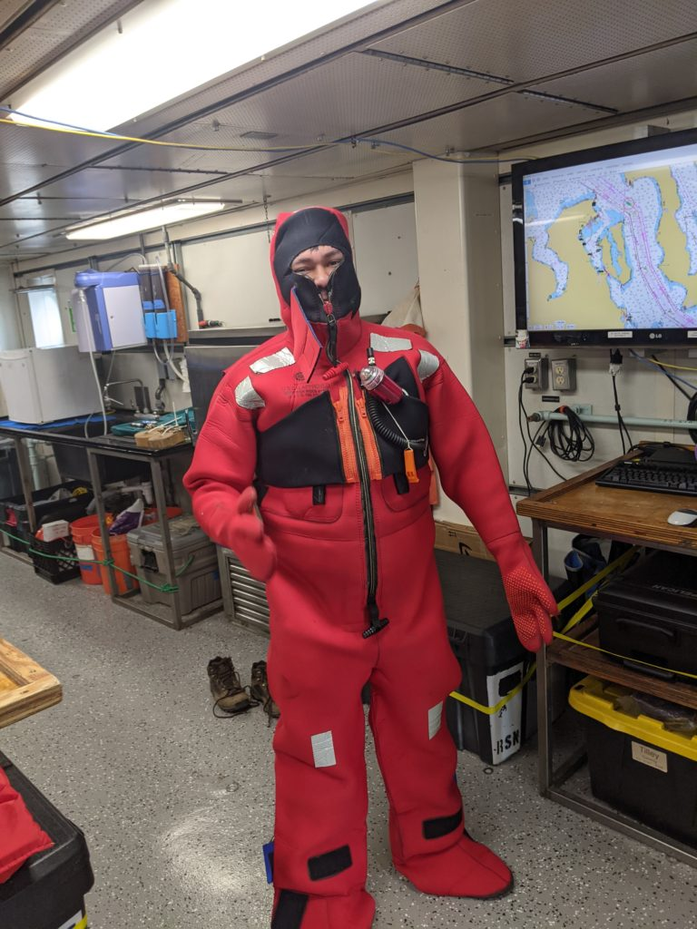 UW School of Oceanography undergraduate Zach Nachod dons an emergency survival suite in preparation for heading out to Axial Seamount during Leg 1 of the RCA VISIONS21 expedition. Credit: Z. Nachod, University of Washington, V21.