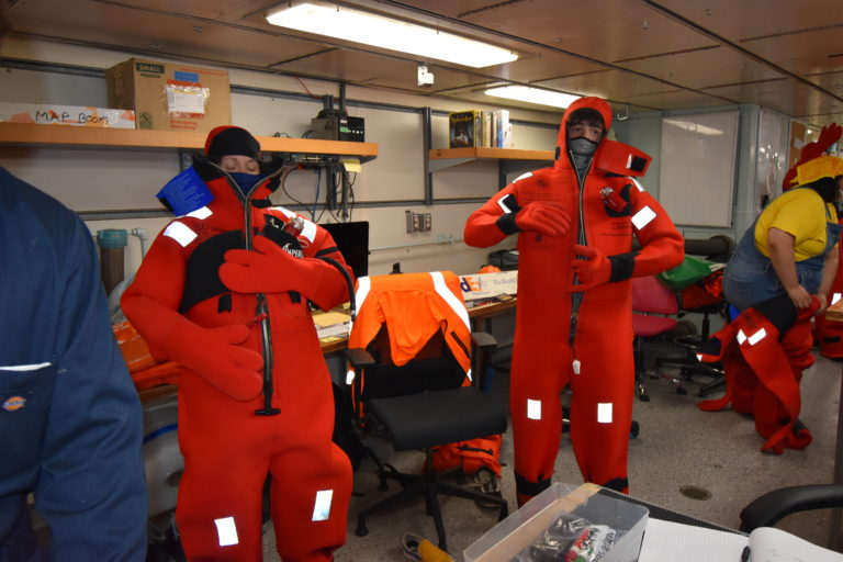 Undergraduates practice donning emergency survival suits in preparation for departure of Leg 1 of the RCA expedition.