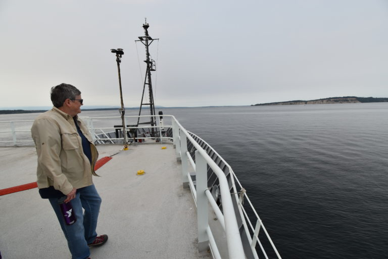 Research Scientist Julie Nelson gazes out to the calm waters of the Salish Sea as the R/V Thompson begins its transit to Axial Base at the start of the RCA 2021 expedition. Credit: M. Elend, University of Washington, V21/.
