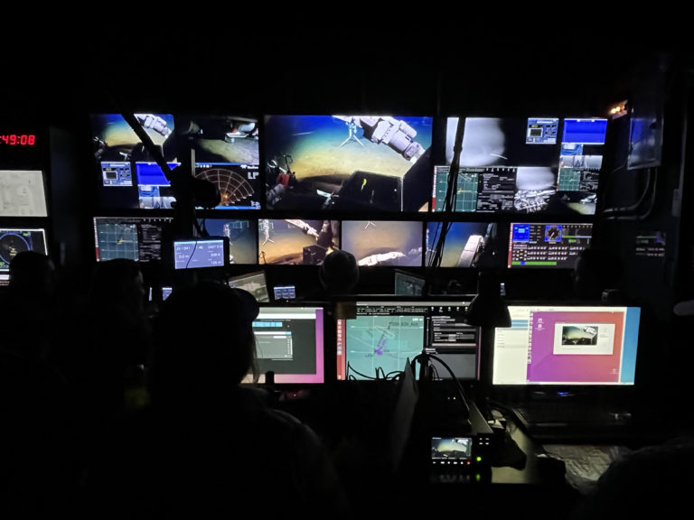 The wall of screens inside the Jason control van is where the pilot, navigator and hotseat are, while the logger and camera positions are behind them. Credit: Z. Nachod, University of Washington.