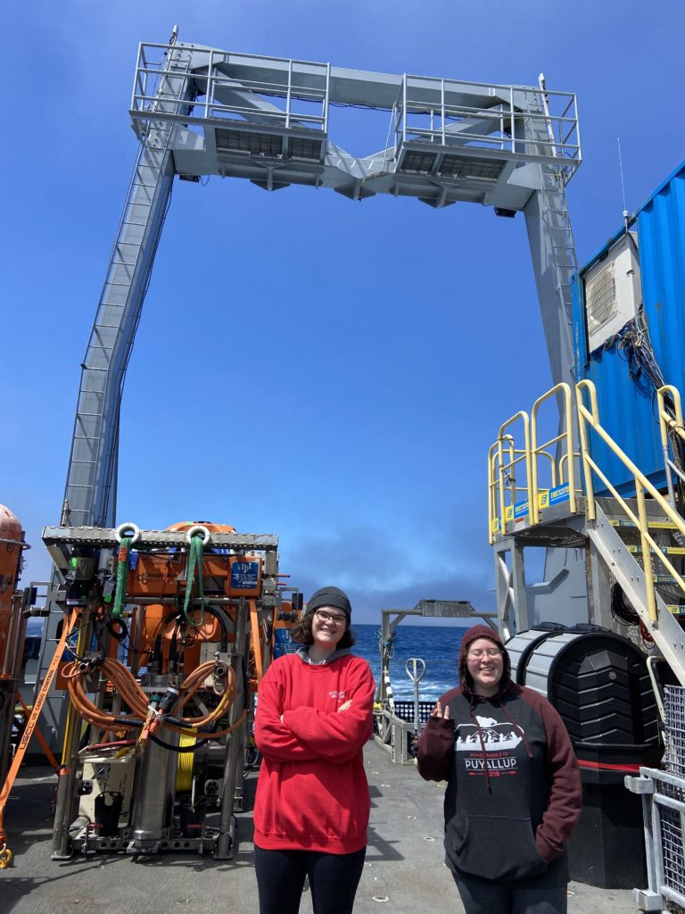 Genevieve and Anabel smile for a quick photo while exploring the back deck in the sun. Credit: J. Willson, University of Washington, V21.
