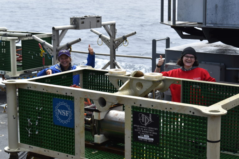 UW undergraduates Jenn Willson and Genevieve Kent, give a thumbs up after cleaning a RCA junction box that had been installed for 7 years at 2600 m water depth. Credit: R. Scott, University of Washington, V21.