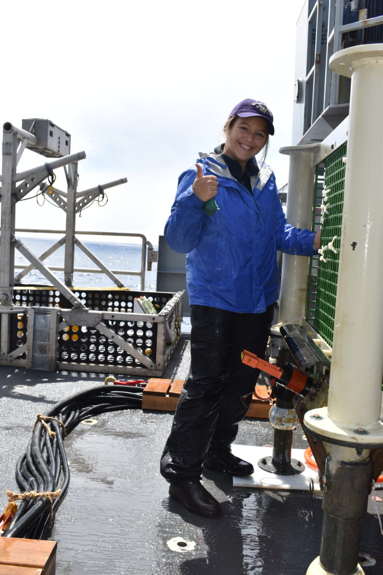 UW undergraduate Jenn Willson gives a thumbs up after cleaning a recovered junction box onboard the R/V Thompson. Credit: R. Scott, University of Washington, V21.