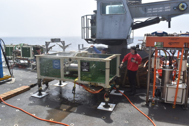 Jenn Willson and Genevieve Kent, clean a junction box recovered from 2600 m beneath the ocean that was installed in 2014. Credit: R. Scott, University of Washington, V21.