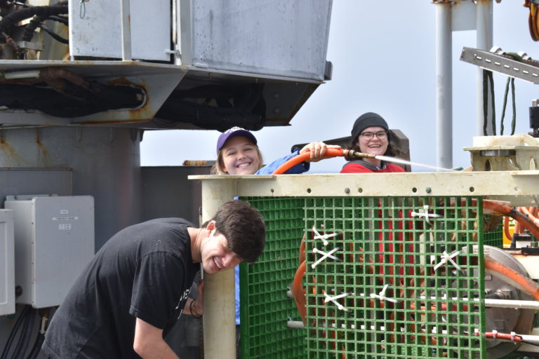 Genevieve, working with Jordan and Andrew to clean a junction box that had been on the seafloor since 2014. Credit: R. Scott, University of Washington, V21.