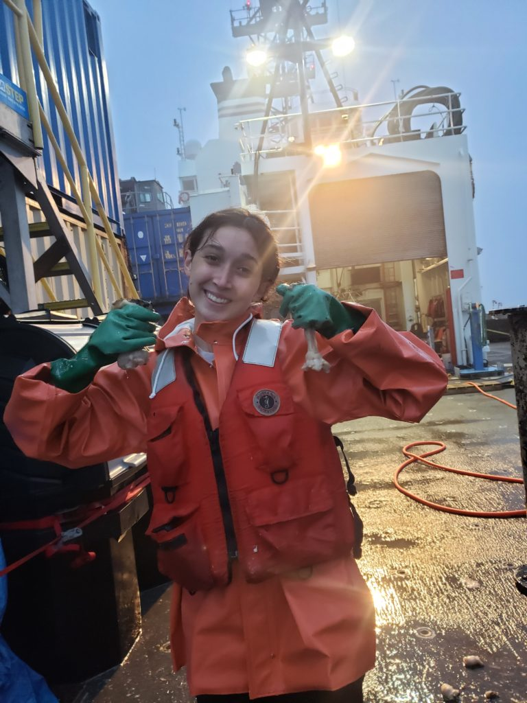 """Sadie Armstron holding up two anemones that she'd pulled off the """"sheep"""" junction box from the Shelf Site. Credit: E. Littell, University of Washington, V21."""