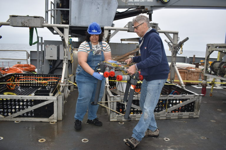 Katie Gonzalez and Orest Kawka moving the FLOBNM101 (multiple orifice sampler and quantitative injection tracer) from the Jason tool basket after recovery from Southern Hydrate Ridge. Credit: M. Elend,  University of Washington, V21.