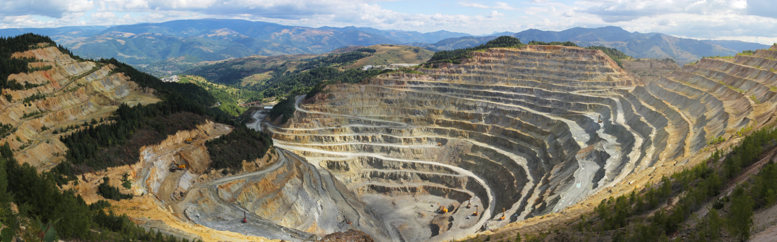 Ariel view of a conflict mineral mine nestled in the mountains with ridges.