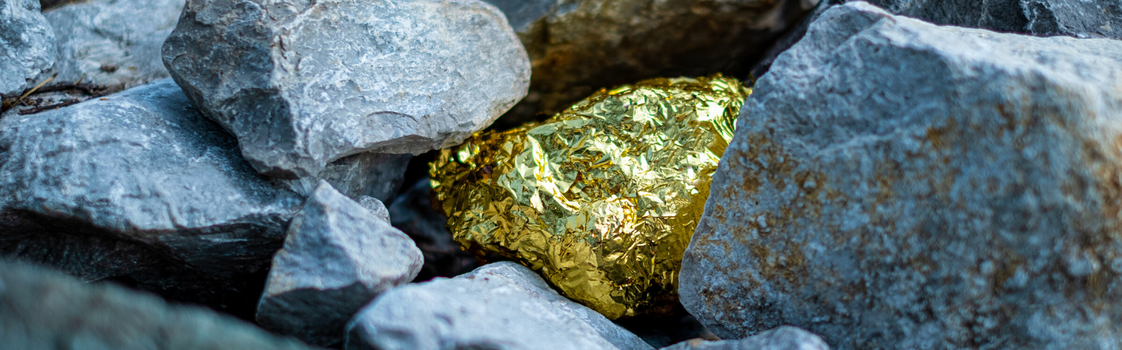 A gold nugget nestled and almost hidden in grey stones in a conflict minerals mine.