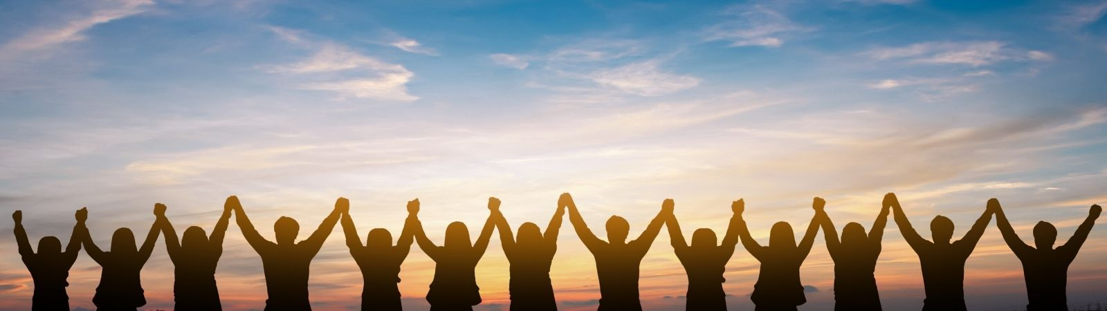 Professionals holding hands above heads in a triumphant, collaborative way facing a beautiful sunset to symbolize ethical, successful business practices.