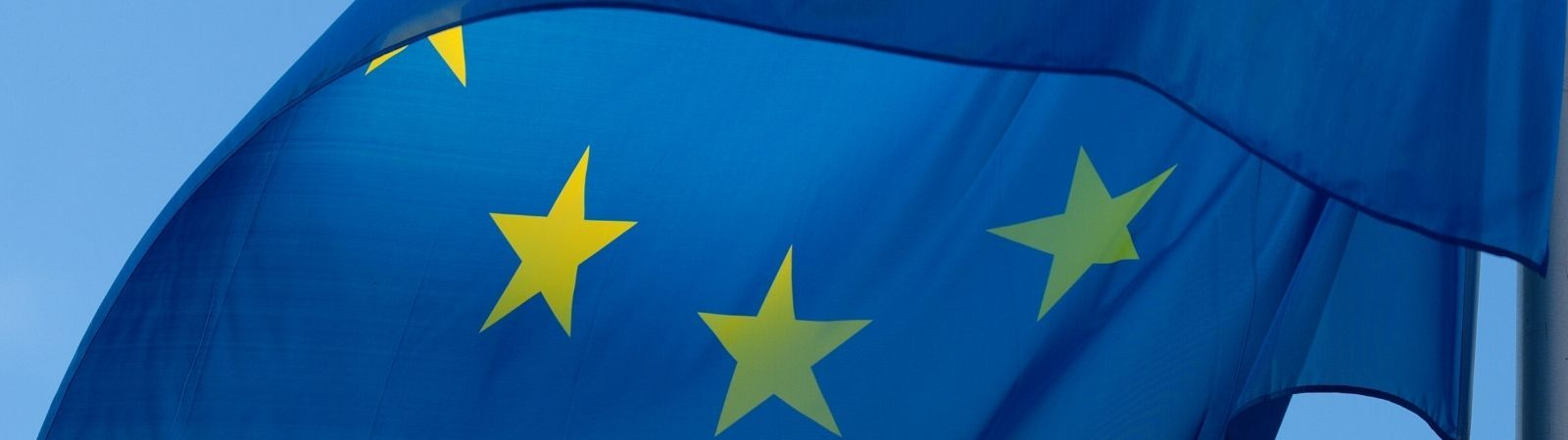 Close up of the EU flag waving in the wind against a bright blue, cloudless sky.