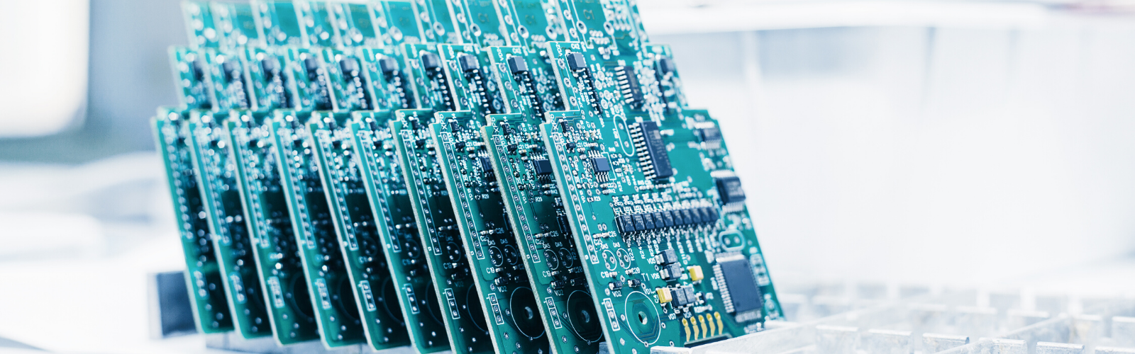 Tray of green circuit boards completed and ready for packaging in a RoHS certified manufacturing facility.