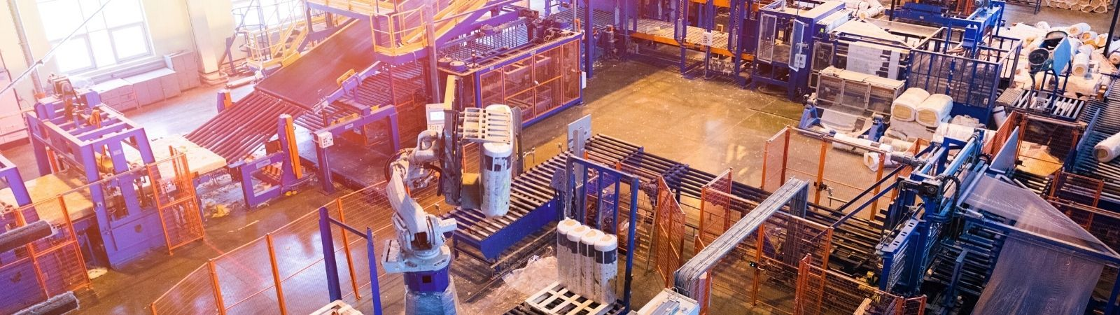 Factory floor image from above with manufacturing machines and blue and red racks.