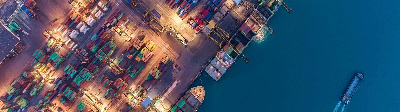 Ariel view of a shipping port with boats in dark blue water and colorful shipping containers on the port side, symbolizing international trade through the USMCA and NAFTA.