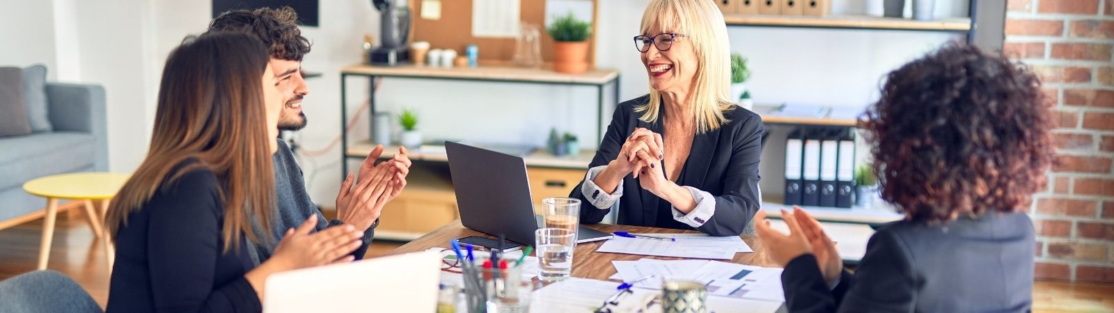 Three professional women and one man sitting around a table in a work meeting smiling and bouncing ideas off one another.