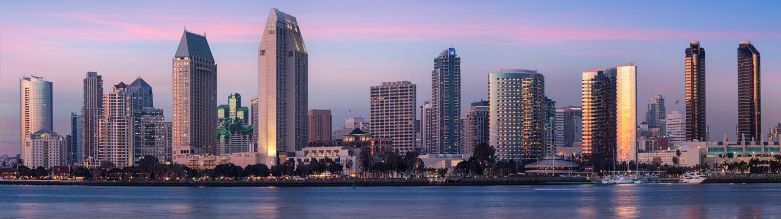 San Diego where Source Intelligence is located  skyline image taken from the bay with a pastel sunset sky behind.