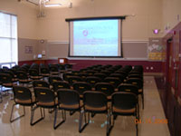 Projector screen in front of rows of chairs.