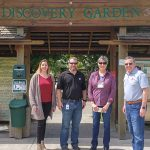 Four people stand in front of entry to the NWREC Discovery Garden.