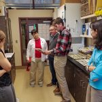 President Kirk and Noel Schulz view research in lab with graduate students.