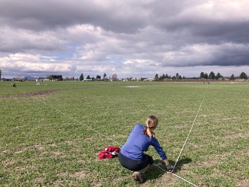 Woman in field measures plot boundaries.