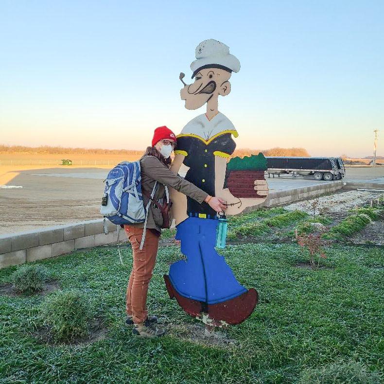 Woman wearing backpack hugs large plywood Popeye figure.