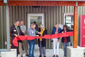 Six people cutting ribbon to dedicate a building.