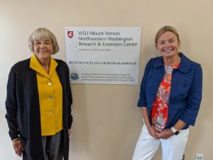 Two women pose with sign dedicating the Ruth Wylie Plant Growth Headhouse.