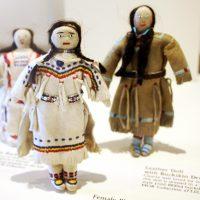Back left, a male Blackfeet doll; center, a female Blackfeet doll, & back right, a leather doll with a buckskin dress.