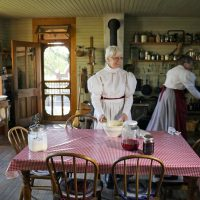 Two female volunteers wearing circa 1880s blouses and dresses cooking in the kitchen of the Tinsley House.
