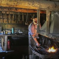 A male volunteer heating metal over an open coal fire in the blacksmith's shop preparing to make a horseshoe.