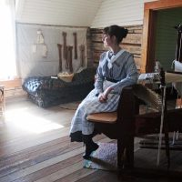 A female volunteer a wearing circa 1880s blouse and dress is seated and looking at a loom in the weaving room of the Tinsley House.