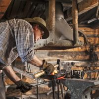Two male volunteers are pounding heated metal in the blacksmith's shop preparing to make a horseshoe.