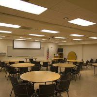 The Redstart Classroom with rounds tables and chairs looking toward the front of the room.