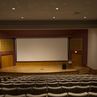 A view of the stage, screen, and podium for the top row of seats in the Hager Auditorium.