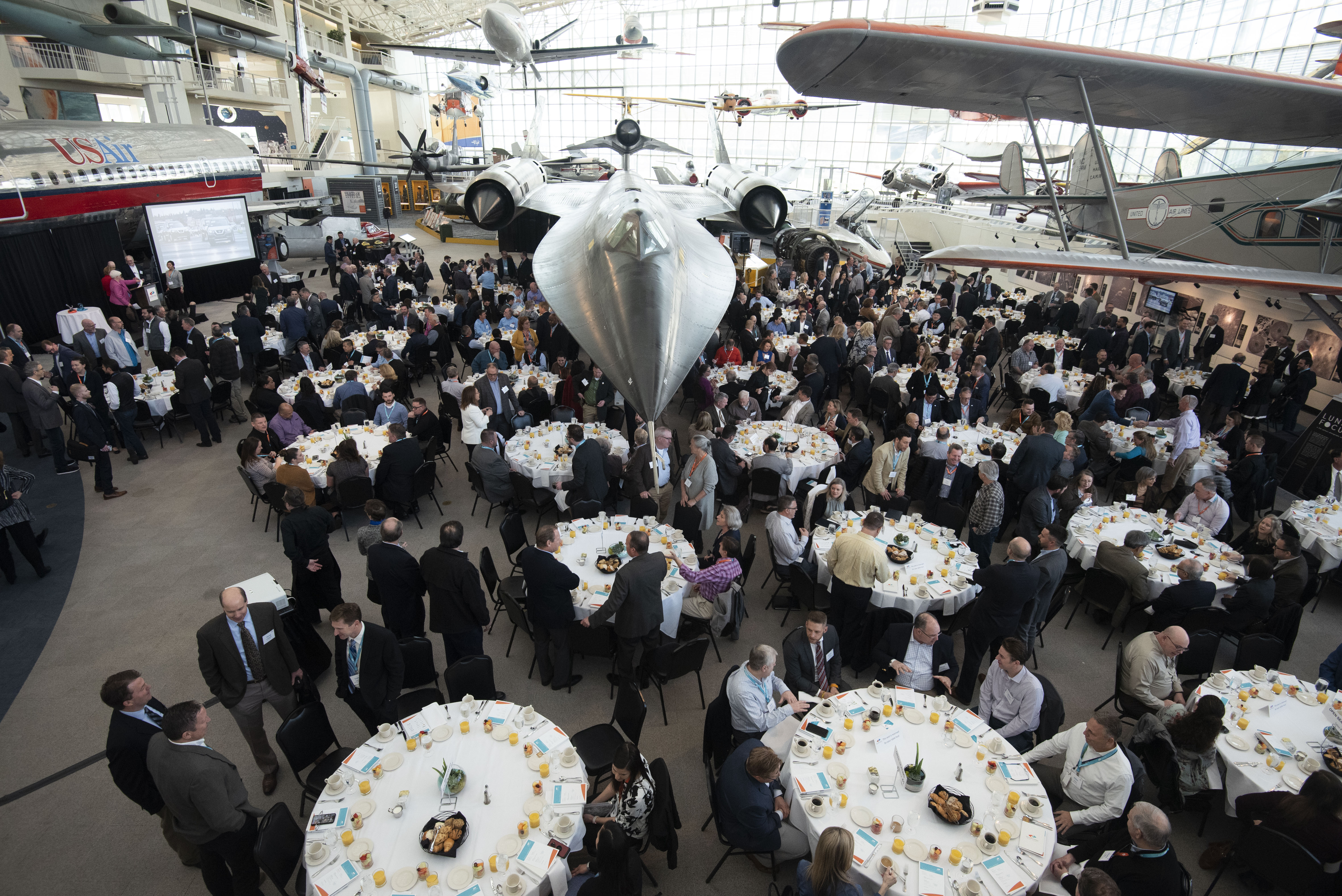 Banquet hall with airplanes displayed above the tables.