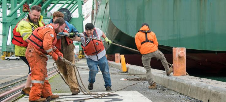 Longshore workers pulling line of a ship