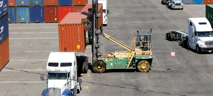 Cargo-handling equipment loading container on truck.