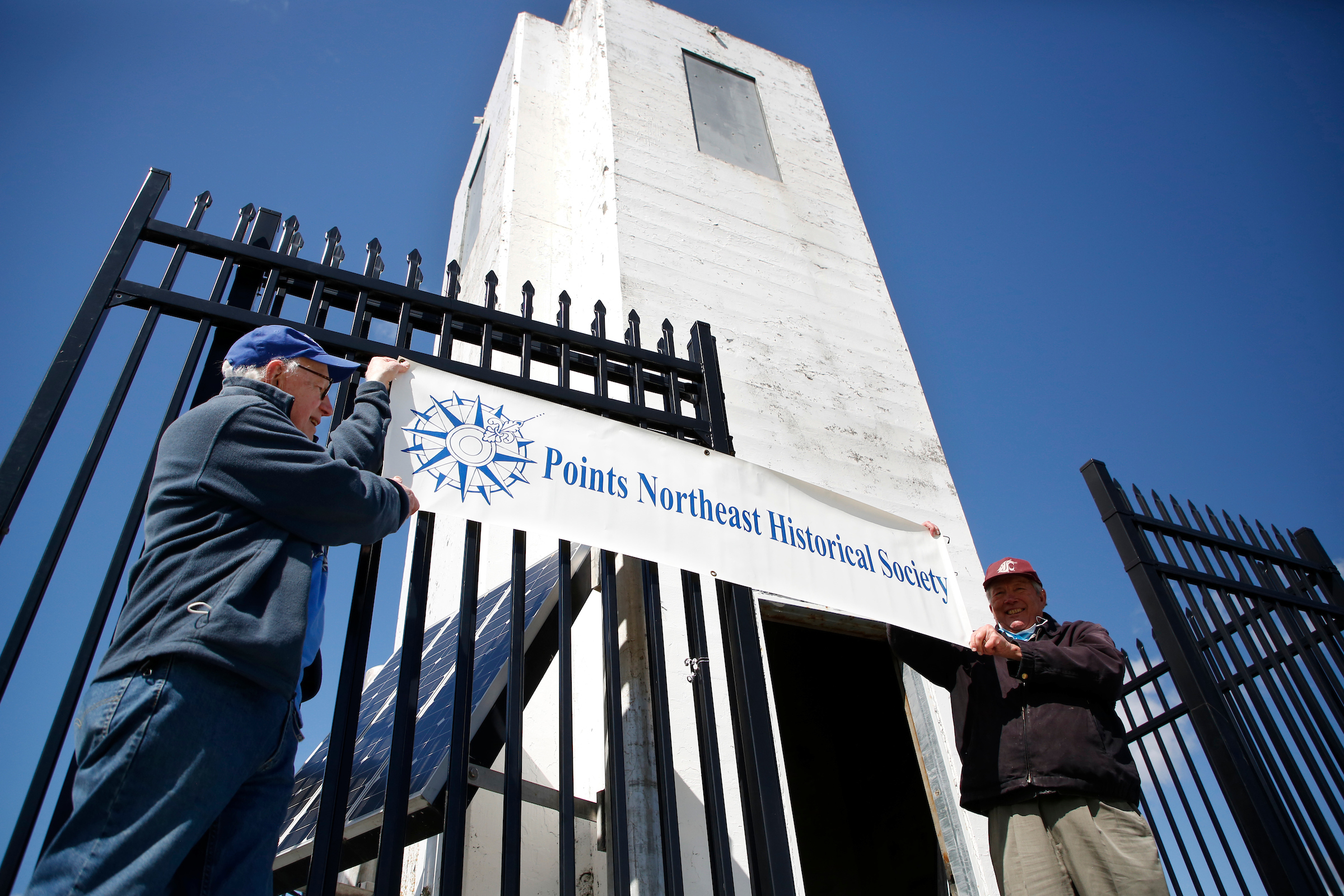 photo of men holding a sign in front of lighthouse