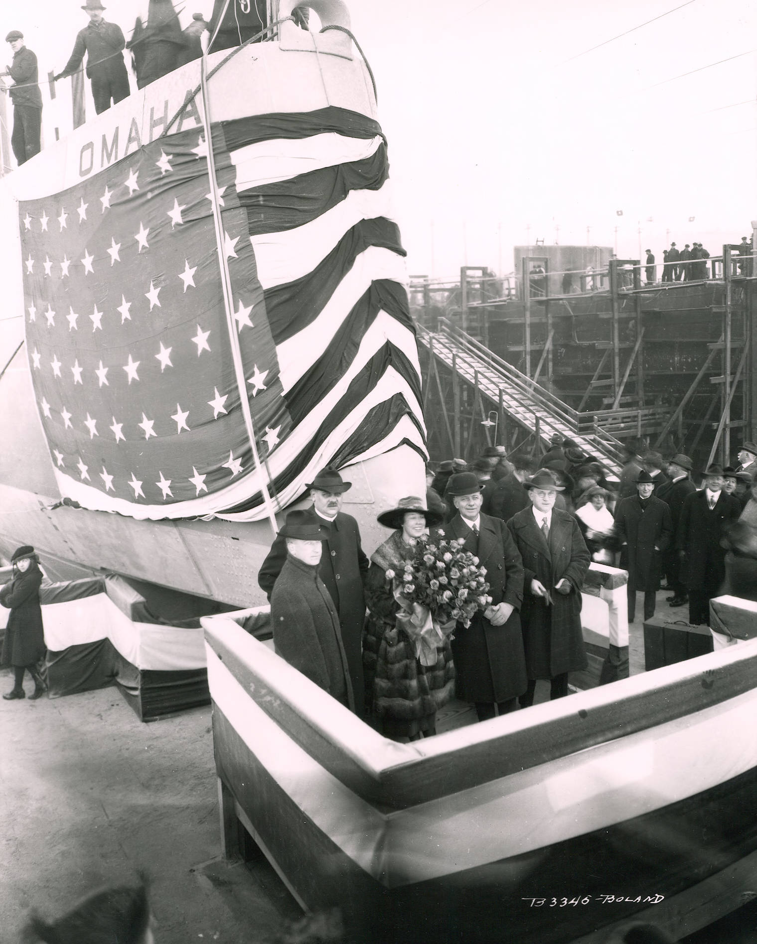 photo of people standing in front of a ship with American flag