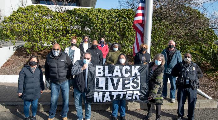 photo of a group of people holding the Black Lives Matter flag