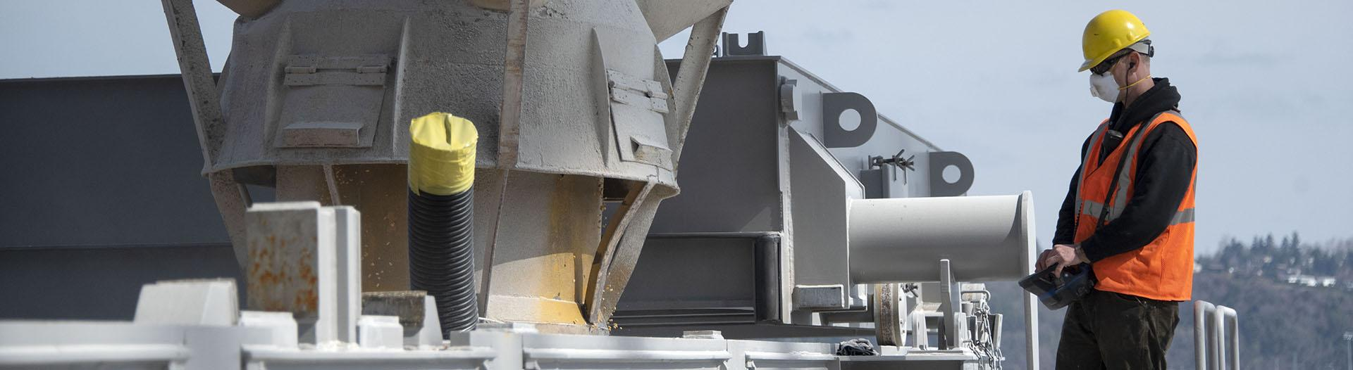 Longshore worker fills a bulk cago ship with grain