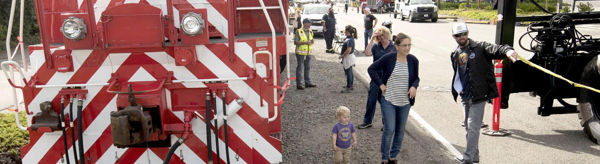 People walking around a Tacoma Rail engine.