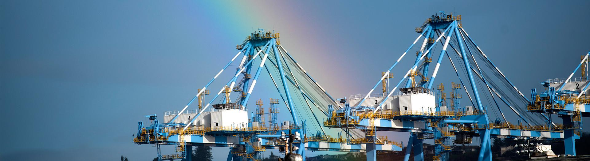 photo of a rainbow over container cranes