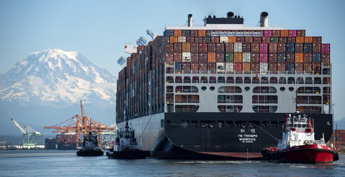photo of a large containership pulled by a tugboat