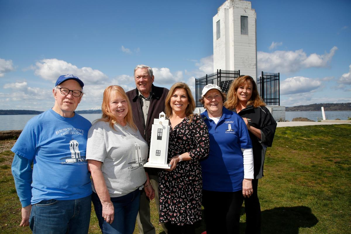 a photo of group of women and men holding a model of the lighthouse and smiling