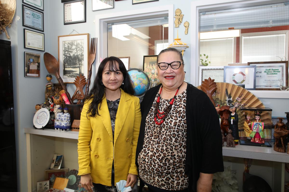 photo of two women standing in front of art displays