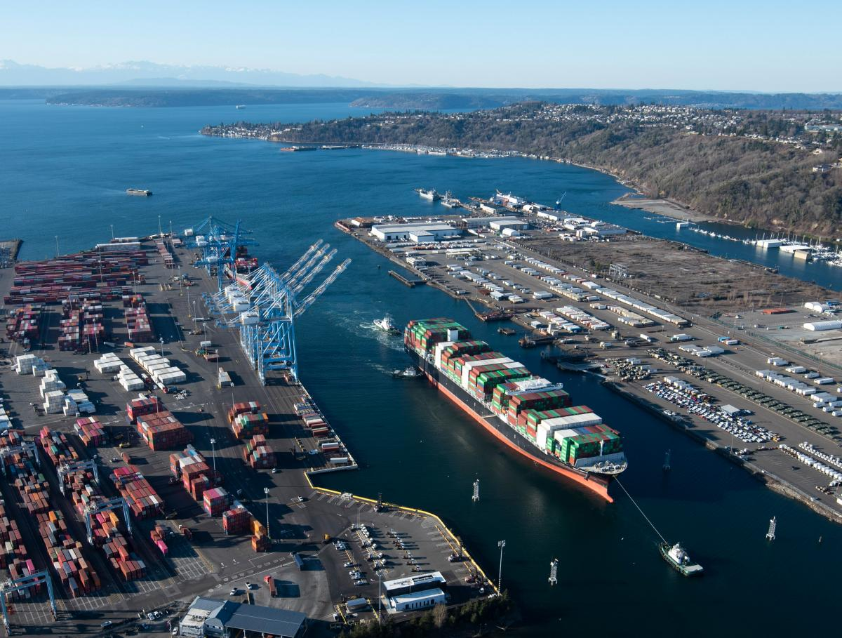 aerial photo of a seaport with a vessel navigating in the waterway