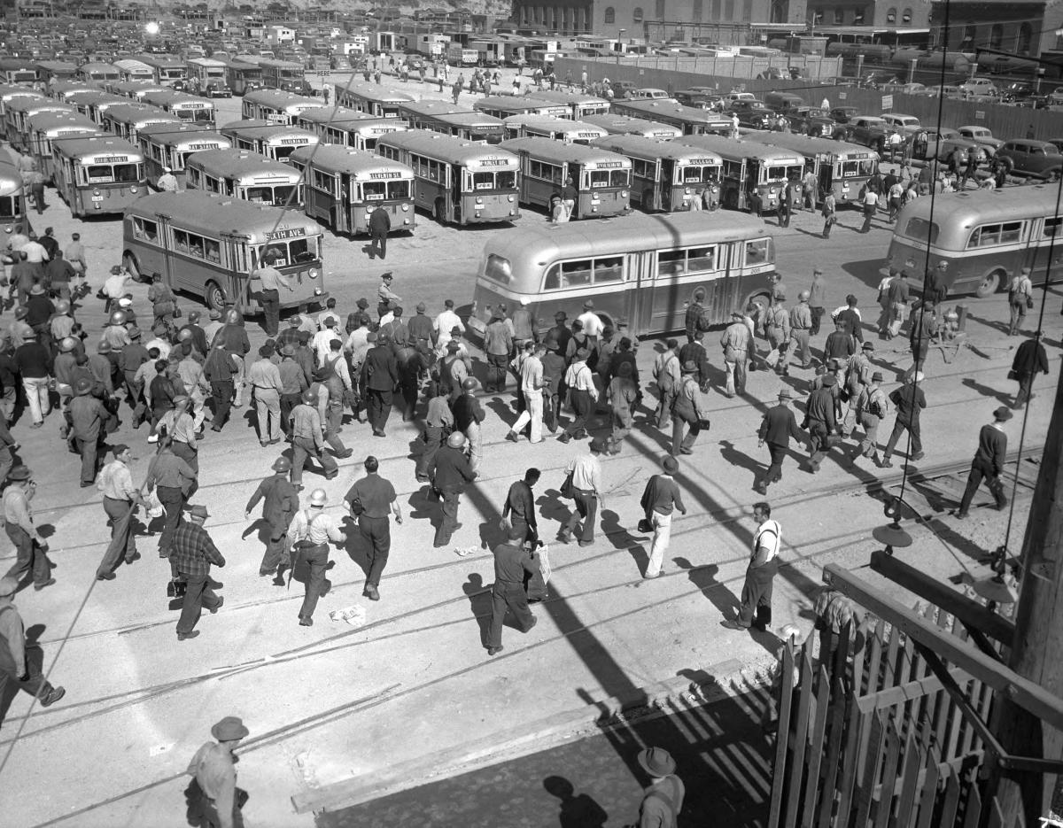 historical photo of people getting out of buses